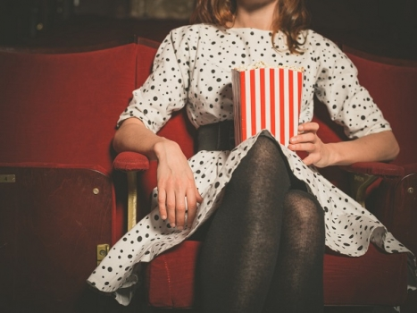 Young woman sitting in movie theater with popcorn Espacio Coruña